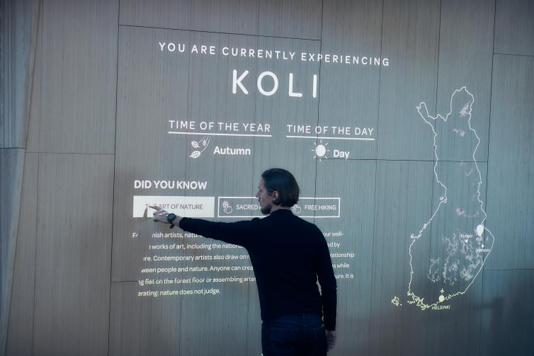 Man interacting with interactive light projection at Helsinki Airport Aukio.