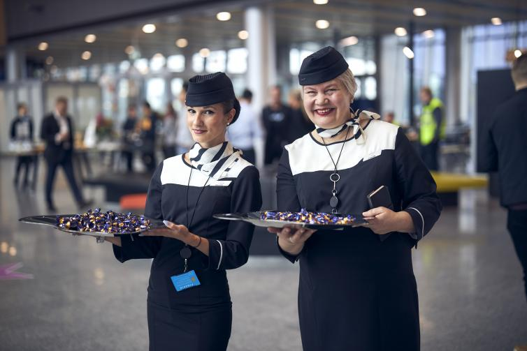 Two smiling Finnair's staff members holding chocolate trays.