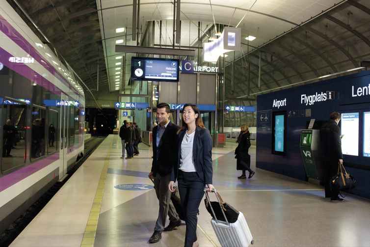Female and male passenger walking towards a train at Helsinki airport train station's platform