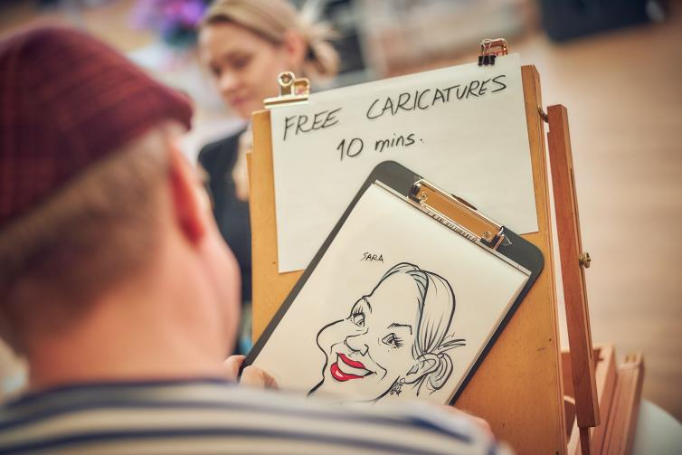 Artist drawing a caricature of a customer.