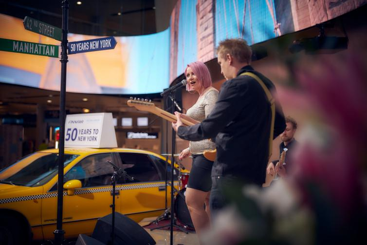 Woman singing and a man playing a guitar at a New York themed event.