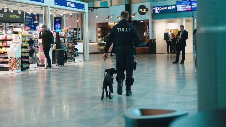Customs sniffer dog and customs officer walking in Helsinki Airport's departure hall.
