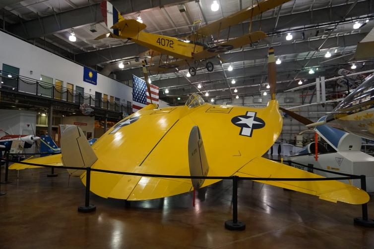 A yellow flat airplane (flying pancake) inside flight museum.
