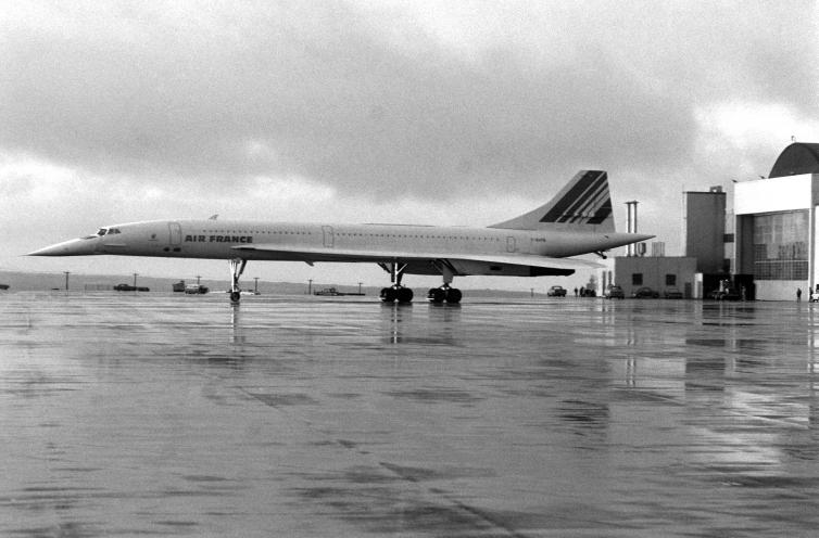 Old black and white photo of an airplane on wet asphalt.