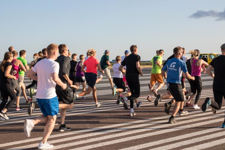 Over fifty people running at runway during cooper test event.