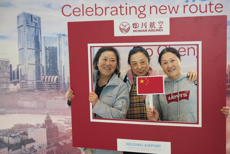 Three ladies posing for pictures holding a flag of China and large red frame.