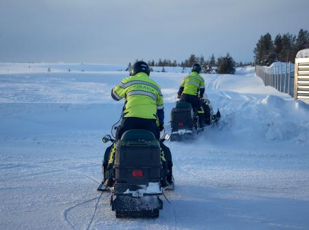 Two airport staff members riding snowmobiles.