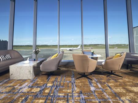 Lounge chairs by floor to ceiling glass windows at Plaza Premium Lounge.
