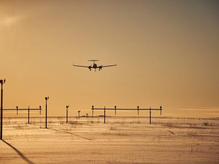 A plane landing in the sunset