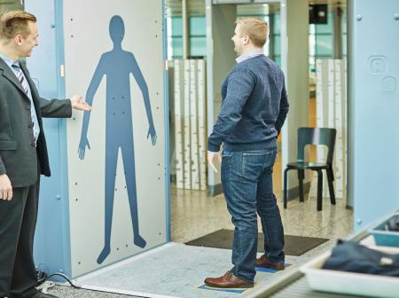 A man standing at a body scanner at airport security.
