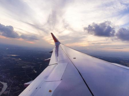 Cabin window view of aircraft wing.