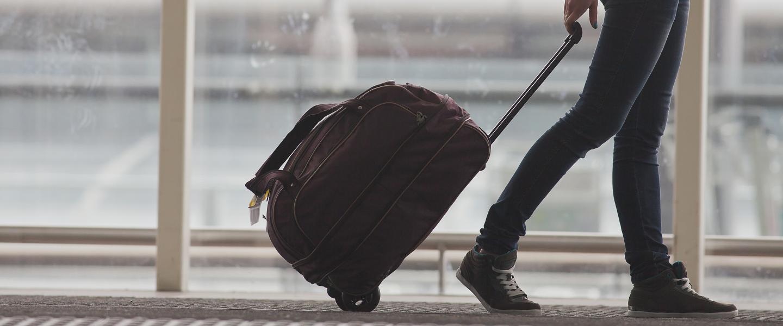 Henkilö kävelemässä matkalaukun kanssa. 9eb6fafe45