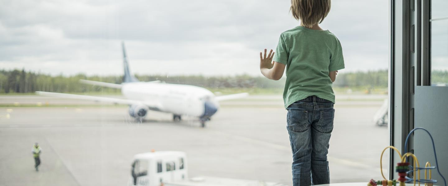 A child is looking at the airplane outside.