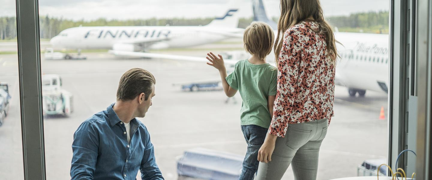 A family is watching airplanes that are on the apron area of the airport.