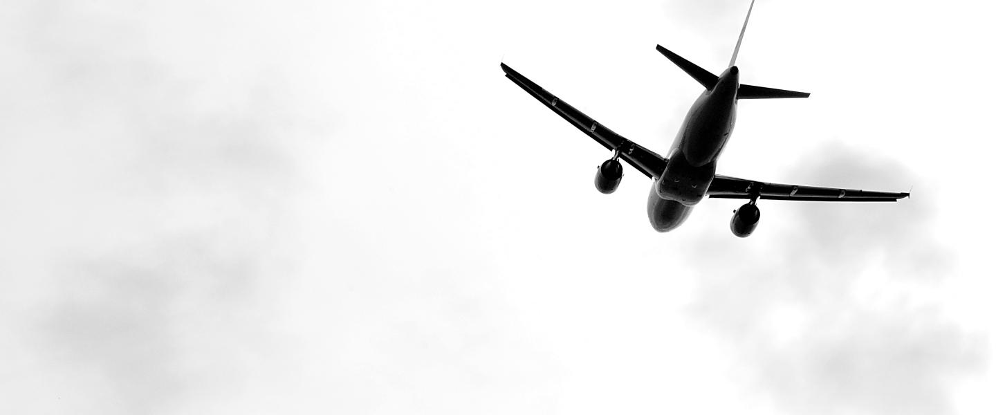 Black and white picture of an airplane flying away.