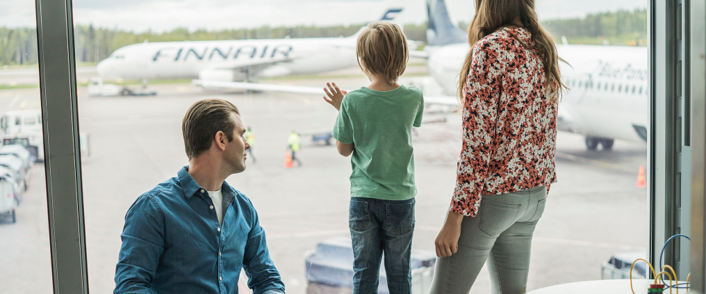 Family watching aeroplane from window in terminal.