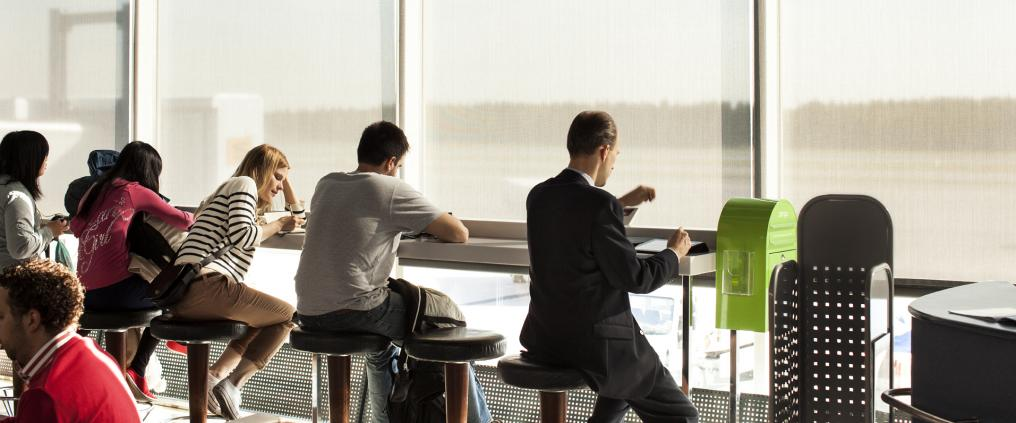Passengers sitting by the window at Helsinki Airport