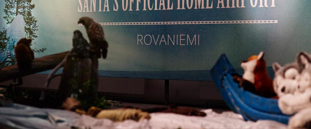 "Some stuffed animals and wall decal that says ""Santa's official home airport, Rovaniemi""."