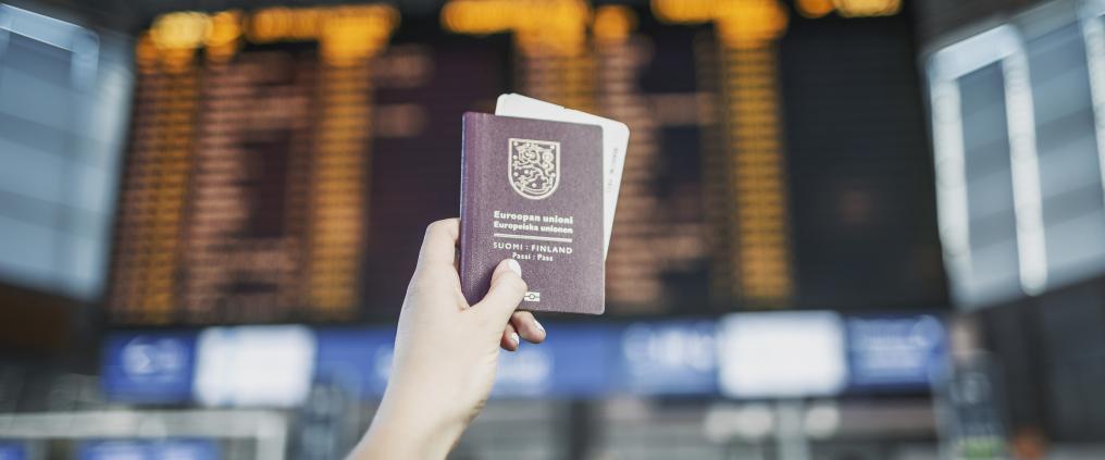 Suomen passi matkustajan kädessä Helsinki-Vantaalla