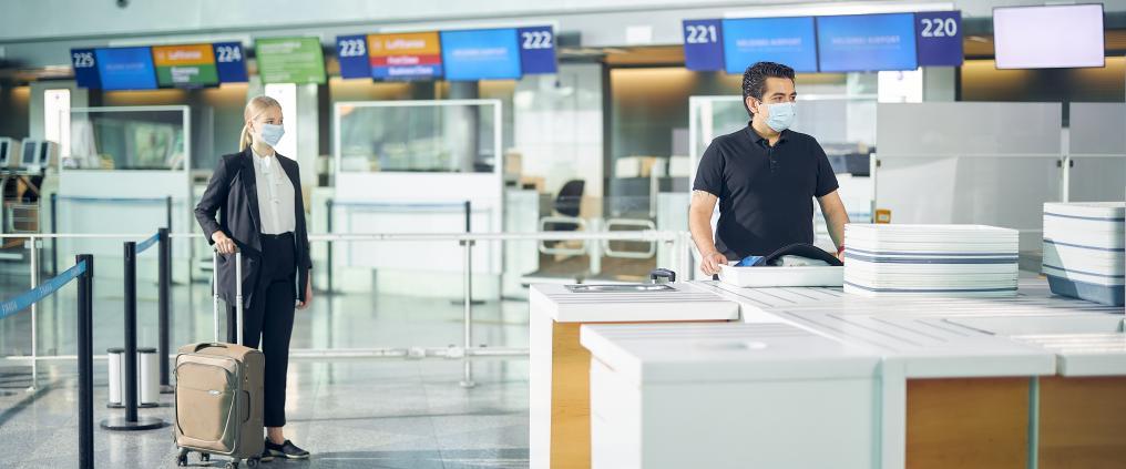 Kaksi matkustjaa turvatarkastuksessa maskit naamalla