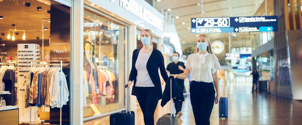 Matkustajia pukeutuneena maskiin Helsinki-Vantaalla