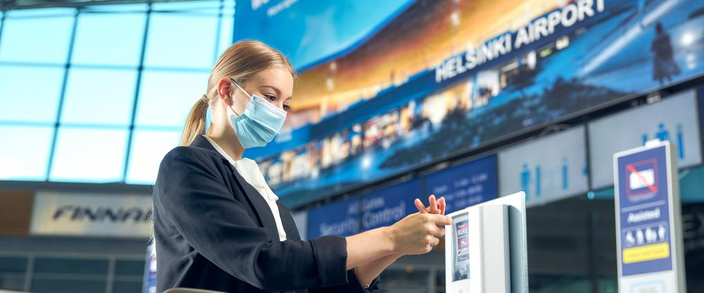 Matkustaja desinfioi käsiään maski naamalla