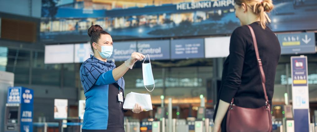 A passenger service person gives a mask for a passengers
