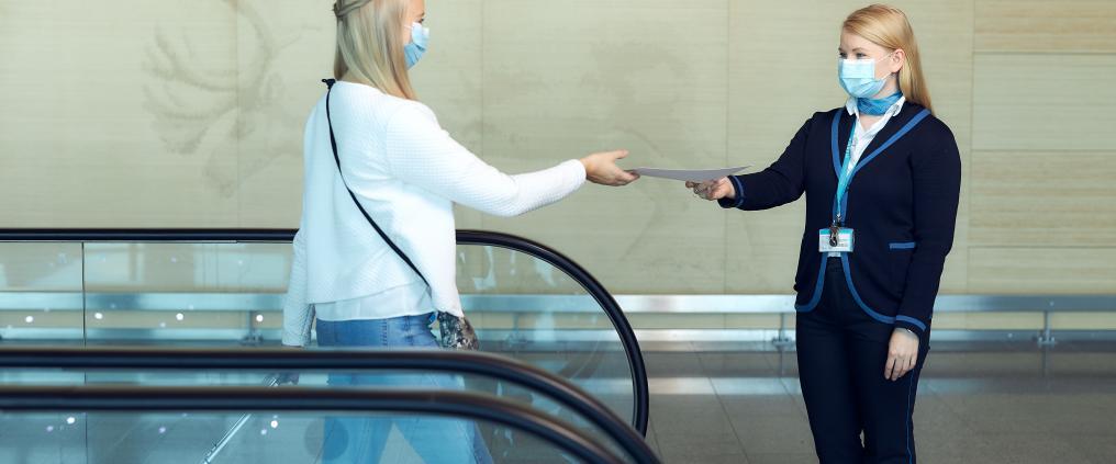 Matkustaja antaa paperin asiakasneuvojalle