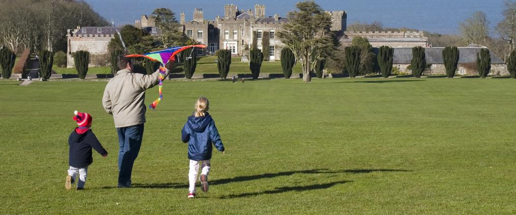 Father and two children are about to fly a kite in grasslands with a castle in the background.