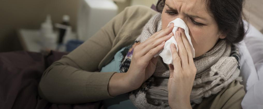 Sick woman blowing her nose into a tissue.