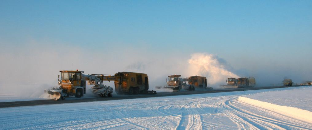 Snowplow machines on snowy day.