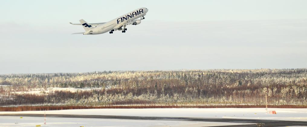 An finnair airplane taking off during winter.