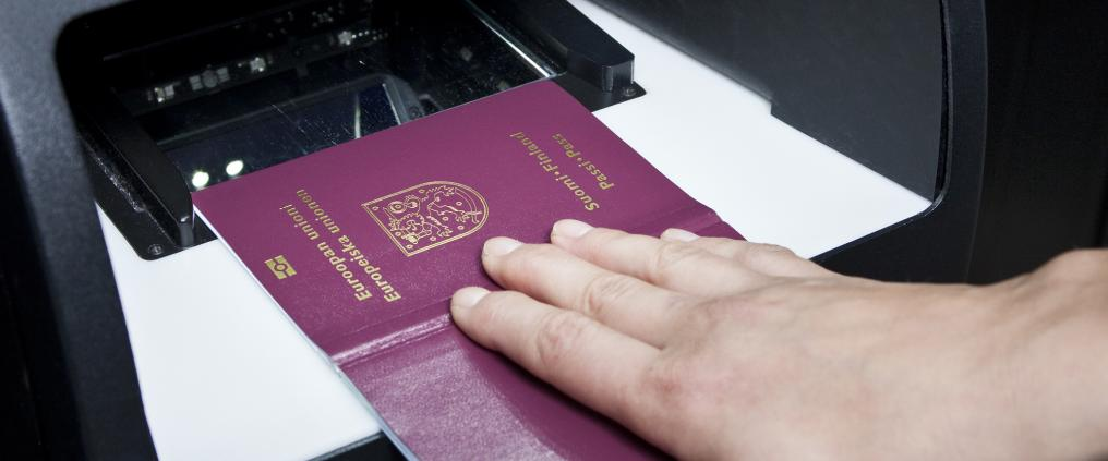 A person placing passport into a scanner.