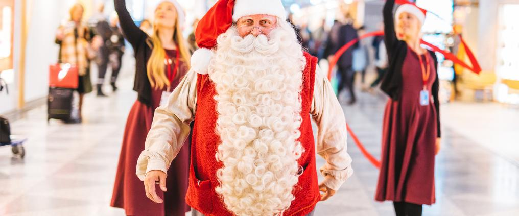 Santa Claus and two performing elves behind him.
