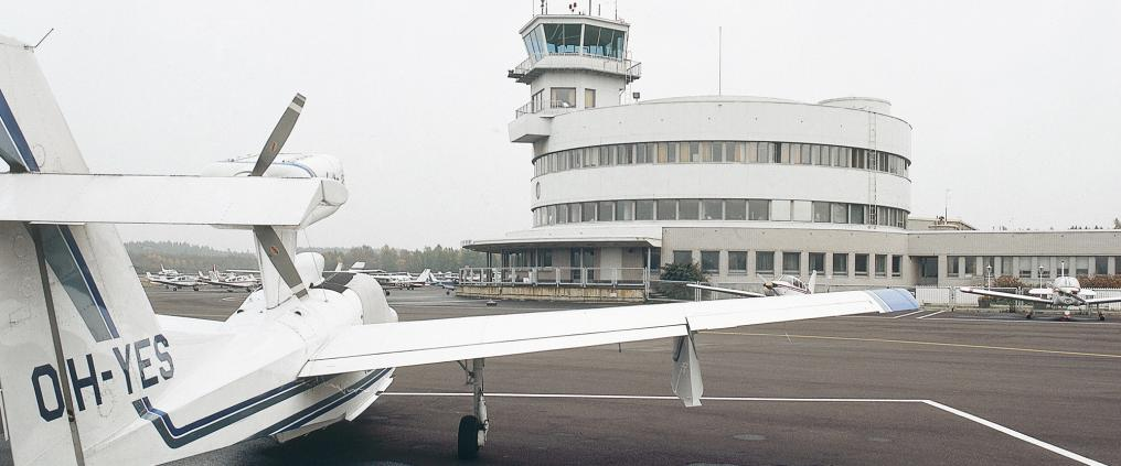 Small aircrafts and a flight control tower at Malmi airport.