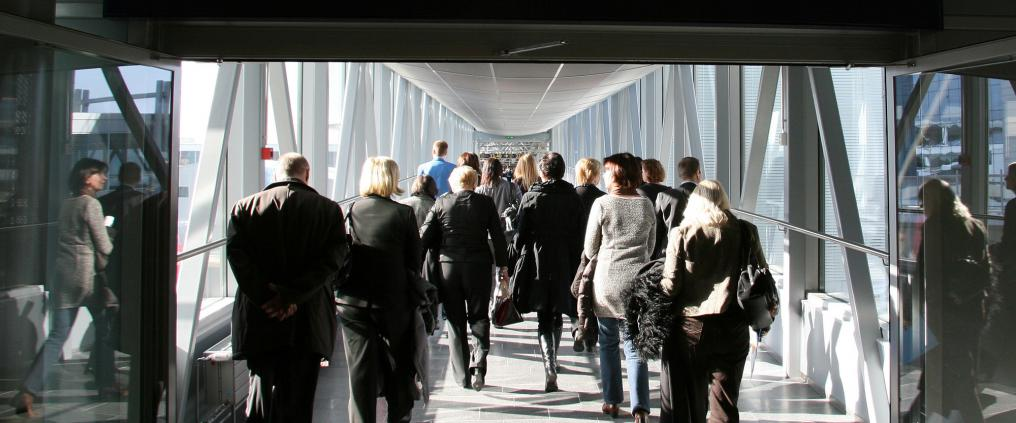 Passengers walking to non-Schengen gates through a glass bridge.