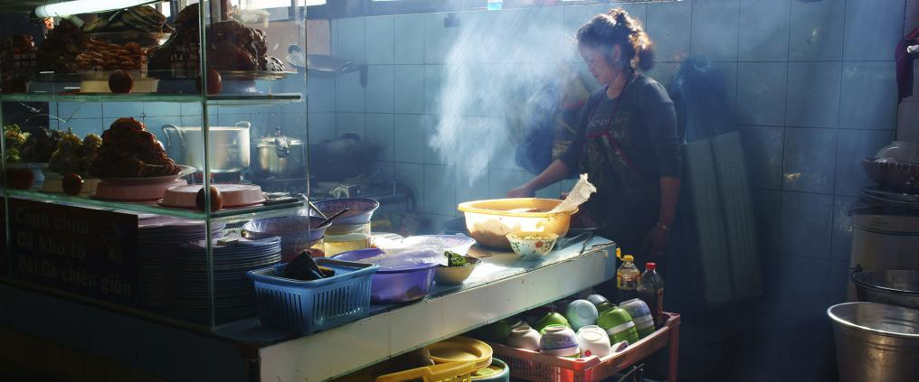 Woman cooking in a vietnamese street food kitchen.