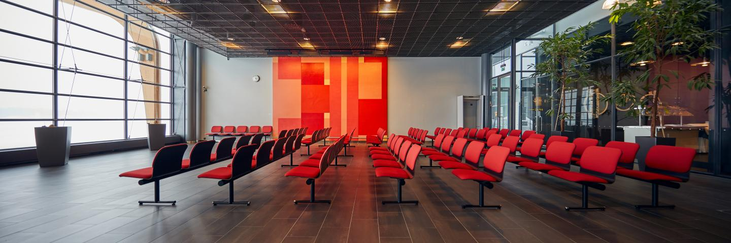 Rows of red chairs at Jyväskylä Airport's waiting area.