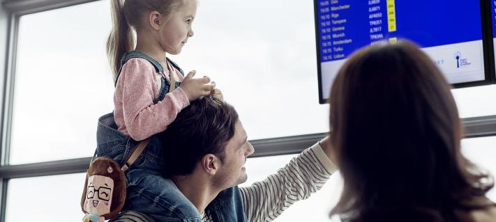 Family of three looking for their flight from flight departure timetable display.