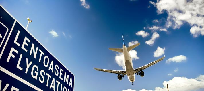 Airplane flying over airport sign.