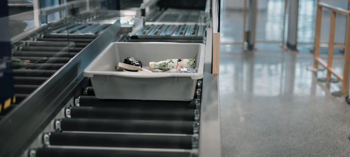 A close picture of the security control line and trays at Helsinki Airport